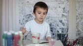 quadro : Cute little preschool boy, drawing picture on mug for his fathers birthday at home, wintertime