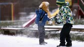 сын : Two boys, brothers, playing in the snow with snowballs, wintertime