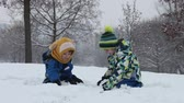 śnieżka : Two boys, brothers, playing in the snow with snowballs, wintertime