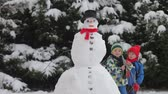 śnieżka : Happy beautiful children, brothers, building snowman in garden and drinking tea, winter time