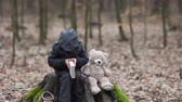 несчастный : Cute little child, preschool boy, sitting on a tree trunk with his teddy bear, reading a book Стоковые видеозаписи