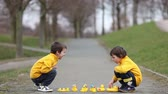 bota : Two adorable children, boy brothers, playing in park with rubber ducks, having fun. Childhood happiness concept Stock Footage
