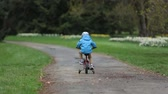 cyklus : Cute little boy, learning how to ride a bike with help wheels in the park, springtime Dostupné videozáznamy