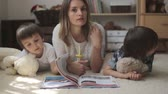 olhando para baixo : Young mother, read a book to her tho children, boys, in the living room Vídeos