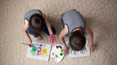 jardim de infância : Two adorable boys, preparing fathers day gift for dad,  painting with hands on a carton at home Stock Footage