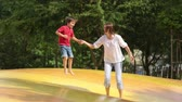 hat : Mother and child jumping on a big trampoline, summertime