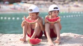 fruit slice : Two little children, boys brothers, eating watermelon on the beach, summertime