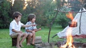 ajudar : Two sweet children, boy brothers, camping outside summertime on sunset, eating potatoes