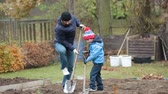 сын : Father and son, working together in garden, autumntime, shoveling the soil for the winter Стоковые видеозаписи