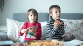 pizza cheese : Two children, boys, eating pizza at home while watching TV