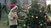 hat : Beautiful school child, boy, decorating Christmas tree on a frosty morning, outdoors, smiling at camera Stock Footage