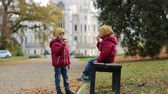 многоцветный : Two beautiful children, boy brothers, sitting on bench in beautiful renaissance castle Hluboka in the Czech Republic