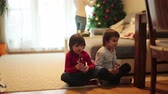 segredo : Two adorable children, boy brothers, eating secretly chocolate candy bar, while mom decorating Christmas tree