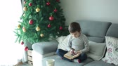 конфеты : Cute school boy, eating chocolate bar and reading a book at home on Christmas