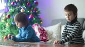 çözmek : Two sweet children, collect puzzles at home sitting on a couch on Christmasm christmas decoration behind them
