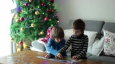 bloco : Two sweet children, collect puzzles at home sitting on a couch on Christmasm christmas decoration behind them