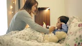 несчастный : Sick boy, lying in bed, mother checking his temperature and giving him medicine