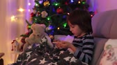 jardim de infância : Cute sweet child, boy, playing on mobile phone under the blanket on first advent Sunday, christmas tree behind them Stock Footage