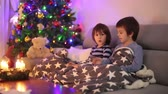 advent decorations : Two sweet children, boy brothers, playing on phone under the blanket on first advent Sunday, christmas tree behind them