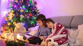 advent decorations : Two sweet children, boy brothers, reading a book under the blanket on first advent Sunday, christmas tree behind them Stock Footage