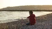 бросание : Two children, playing on the beach with rocks, wintertime on sunset