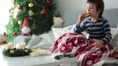 tecido : Little child, boy, blowing his nose and sneezing, lying sick in bed on Christmas