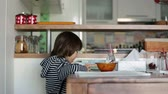 зерно : Cute little boy, eating breakfast and playing on mobile in the kitchen at home, smiling happily