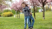 springtime : Two children, brothers, fighting in a park, springtime Stock Footage