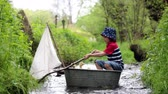 duck : Cute child, boy, playing with boat and ducks on a little river, sailing and boating. Kid having fun, childhood happiness concept