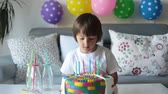 подарок : Sweet little child, boy, celebrating his sixth birthday, cake, balloons, candles, cookies. Childhood happiness concept Стоковые видеозаписи
