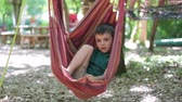 položit : Cheerful child playing and lying inside the hammock, summertime Dostupné videozáznamy
