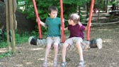 springtime : Cute children, boy brothers, swinging on a big rope swing in amusement park, summertime