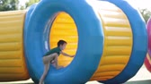 globo : Cute little boys, playing in a rolling plastic cylinder ring with a hole in the middle, outdoor