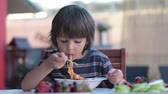 noodle dish : Cute child, preschool boy, eating spaghetti for lunch outdoors in garden, summertime