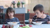 molho : Cute children, preschool boys, eating spaghetti for lunch outdoors in garden, summertime