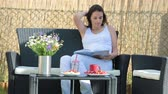 mensagem : Young pregnant woman, having healthy breakfast, coffee, fruits and reading a book in a backyard garden Vídeos
