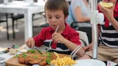 hranolky : Preschool child, eating big steak of meat and french fries at a restaurant