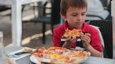 fast food : Happy little boys, sitting at table in restaurant, eating pizzas, sitting at table in restaurant, eating pizza