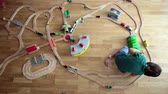 jardim de infância : Sweet preschool child, playing with wooden railway and trains at home, top view Stock Footage