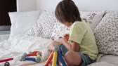 instrukce : Sweet preschool child boy playing with toys indoor, sitting in bed