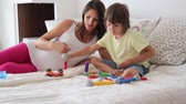 instrukce : Cute pregnant mother and child boy playing together indoors at home with toys