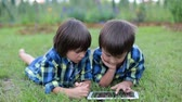 positividade : Two preschool children, boy brothers, playing on tablet, lying down in the grass in garden, backyard