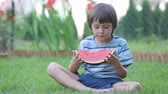 slices : Happy little child, boy with watermelon in a garden, summertime