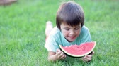 positivo : Happy little child, boy with watermelon in a garden, summertime