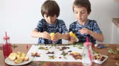 borboleta : Sweet children, boys, applying leaves using glue while doing arts and crafts in school, autumn time