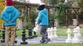 checkmate : Two children, boy brothers, playing chess with huge figures in the park on the ground, autumn time. Childhood happiness concept, kids playing in the park fall time