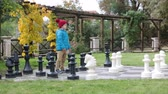 vibrante : Two children, boy brothers, playing chess with huge figures in the park on the ground, autumn time. Childhood happiness concept, kids playing in the park fall time