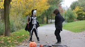dia das bruxas : Two children in the park with Halloween costumes, having fun