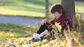 листва : Adorable little boy with teddy bears in the park on a autumn day in the afternoon sitting on the grass Стоковые видеозаписи