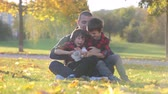 prato : Cute funny children, playing with their father in the park, autumn time, nice afternoon back light Stock Footage